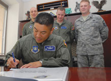 (U.S. Air Force photo/Staff Sgt. Stacy Foster) Col. Cary Chun, 50th Space Wing commander, signs Schriever's first Air Force Assistance Fund donation form delivered by AFAF representatives Capt. Douglas Hale, 4th Space Operations Squadron, Capt. Coy Harvey, 4th SOPS, and Master Sgt. Stephen Campbell, 50th Space Communications Squadron. The AFAF campaign began March 23 and runs to May 1.