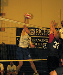 (U.S. Air Force photo/Scott Prater) Jeremy Brown spikes as Randy Hillsgrove goes up for a block during 4th Space Operations Squadron's semifinal victory over 50th Space Communication Squadron March 31 in the Schriever intramural volleyball tournament at the fitness center.