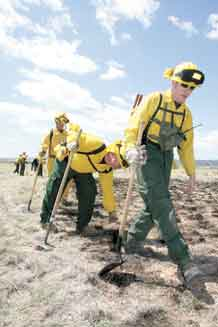 Firefighting students taking part in Fort Carson's Wildland Academy check the perimeter of a smaller burn area May 8 as part of their training.