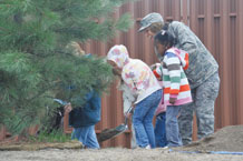 (Air Force photo by Robb Lingley)  Col. Emily Buckman, 21st Mission Support Group commander, assists children enrolled in Peterson's main base child development center plant a Ponderosa Pine at Peterson's West Gate Visitor Center May 1. Three Ponderosa Pine trees were planted in commemoration of Arbor Day, April 24. Peterson was consecutively designated Tree City USA for the 15th year and received the eighth Tree City USA Growth Award for increasing the number and density of trees.
