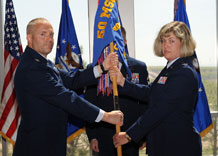 Lt. Col. Ruth Spencer, 50th Contracting Squadron commander, accepts the guidon from Col. Edward Baron, 50th Mission Support Group commander, during an assumption-of-command ceremony held in the atrium of he DeKok Building June 12.