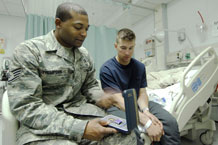 Staff Sgt. Christopher Thompson, Chapel Operations NCOIC, with a wounded warrior while assigned to Bagram Air Field hospital.  Courtesy Photo