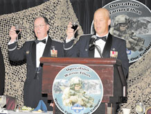 """Gen. C. Robert Kehler, commander Air Force Space Command, and Col. Jay Raymond, 21st Space Wing commander, charge their glasses for a toast during the """"Operation Warrior Ethos"""" Dining Out July 17. The event, sponsored by the Rocky Mountain Company Grade Officer Council, was a unique fusion of formal trappings and combat-themed elements, and was Peterson's culminating event for the Air Force Space Command Year of Leadership, which focused on warrior ethos during the month of July. About 500 Airmen, Soldiers, and Canadian servicemembers attended the event. (Air Force photo by Roberta McDonald)"""