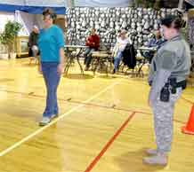 """Chris Grayson, left, Army Space and Missile Defense/Armed Forces Strategic Command at Peterson Air Force Base tries to walk the line while wearing """"drunk goggles."""" Spc. Joelene Raciborski, traffic investigator, 148th Military Police Detachment, 759th Military Police Battalion, watches as Grayson misses the line."""