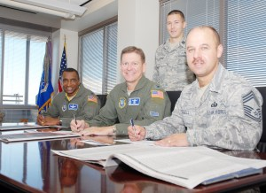 U.S. Air Force photo/Staff Sgt. Stacy Foster Col. Wayne Monteith, 50th Space Wing commander, flanked by Col. Kenneth Allison, 50 SW vice commander, and Chief Master Sgt. Michael Whetsell, 50th Network Operations Group, sign their Combined Federal Campaign donation forms as Capt. Phillip Ervie, 50th Space Wing CFC project officer looks on. Schriever's goal in this year's campaign is $250,000. After the first week of donations, Schriever has met 25 percent of its goal.