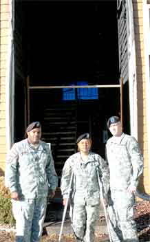 Staff Sgt. Larry Sanders and Staff Sgt. Angel Sims, Division Special Troops Battalion, 4th Infantry Division, and Spc. Justin Janda, Headquarters and Headquarters Company, 759th Military Police Battalion, stand in front of the building where they alerted residents of a Nov. 7 fire.