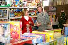 Maj. Gen. David G. Perkins, commanding general, 4th Infantry Division and Fort Carson, gets a tour of Santa's Workshop from elf Crista McCormick Dec. 4 at Alternate Escapes.