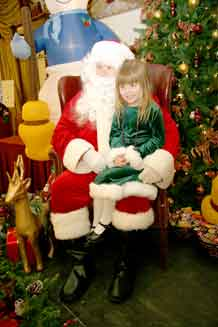 Photo by Rick Emert.  Family member Kristin Harris, 5, sits on Santa's lap Sunday at the Santa's at the Elkhorn event at Elkhorn Conference Center. Kristin asked for a Nintendo DS game.