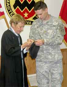 Photo courtesy of Leigh Anne Rambus.  Maura Kaley, mother of Lt. Col. David Kaley, executive officer, 3rd Battalion, 16th Field Artillery Regiment, 2nd Brigade Combat Team, 4th Infantry Division, pins the rank of lieutenant colonel onto her son's beret during a promotion ceremony Jan. 4.