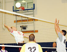 """By Scott Prater Schriever Sentinel Ross Wetmore and Doug Hale aren't used to playing for the same team. Last year, the players faced off against each other in the Schriever Intramural Volleyball Championship game, Wetmore set for eventual champion 2nd Space Operations Squadron while Hale hit for eventual runner up 4th Space Operations Squadron. This year's league looks quite a bit different, however, as many of the base's best players have either switched squadrons, or changed teams for any number of reasons. So the odd form of musical chairs brought Wetmore and Hale together along with Lester Lorenz and Tammy Tucker for Feb. 23's season opener at the fitness center. The group makes up the core of the dual-squadron team 50th Operations Support Squadron/50th Operations Group Standardization and Evaluation Division, which knocked off 50th Civil Engineer Squadron 25-20, 25-20 to start the season on a winning note. """"This was really the first time we've all managed to get together,"""" said Wetmore, the team's captain. """"Doug and Lorenz are going to be our main hitters, and really, it's nice having two. That way you always have one of them hitting in every rotation."""" Thanks in part to its scrappy defense, 50 CES kept both games tight early on, but it was Tucker who took over in the first game. With the teams tied at 6-6, she stepped to the service line and promptly served for the next 11 points. Wielding a wicked dip serve, Tucker handcuffed 50 CES receivers on nearly every point and helped 50 OSS/OGV build an insurmountable lead. In a second game dominated by errant hits, off-balance sets and rusty play, the teams traded points most of the way. 50 CES led 17-14 before Hale and Lorenz found their hitting rhythm and 50 OSS/OGV managed to pull away. """"Their defense surprised me,"""" Hale said of his 50 CES opponents. """"They picked up a lot of balls I didn't think they could get to... and then they turned them around on us. I don't think we were prepared for that."""" Once again it was"""