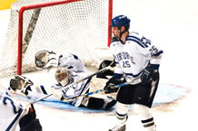 Senior goalie Andrew Volkening successfully defends the goal as Sophomore Tim Kirby assists. Air Force defeated Army 4-2 at the Cadet Ice Arena Mar 13.  Photo by Bill Evans