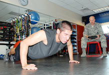 Airman 1st Class Warren Malcolm III attempts to get one last pushup in before his time runs out while Master Sgt. Garrett Maynard times him during the 50th Security Forces Squadron Guardian Challenge team tryouts March 11.  (U.S. Air Force photo/Staff Sgt. Daniel Martinez)