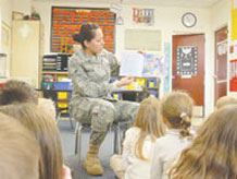 "Airman 1st Class Shelby Manuelito, 21st Force Support Squadron, reads to kindergartners March 8, in Tina Ferguson's class at Christa McAuliffe Elementary School in Colorado Springs School District 11. Peterson Air Force Base recently launched an ""Adopt A School"" program where Airmen and civilians can volunteer in area schools. District 11 school officials say there are endless volunteer opportunities for Airmen to be mentors, readers, lunch buddies and more. For more information about the program call Lisa Ballard, Peterson school liaison, at 556-7596. (U.S. Air Force photo/Monica Mendoza)"