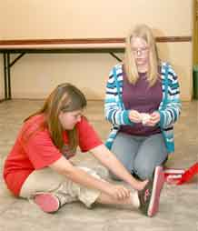 "Krystal Fortner, left, and Sabrina Hulshof demonstrate first-aid procedures at a ""Self-advocates, Outgoing, Achieving goals and Responsible citizens"" session April 9."