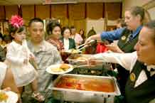 Elkhorn Conference Center staff serve sweet-and-sour ham and teriyaki chicken to attendees at the Asian/Pacific Islander Heritage Celebration Monday.