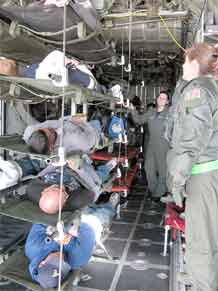 Warrior Transition Battalion Soldiers lie in racks of transport litters inside a Wyoming Air National Guard C-130 aircraft while receiving instructions from the plane's crew. The Soldiers portrayed injured civilians who were notionally transported from Utah.