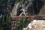 The narrow-gauge train hugs the mountainside for most of the 20-mile journey, following close to the trail taken by thousands in the Klondike Gold Rush of the 1890s while passing over wooden trestles and through narrow tunnels. Photo courtesy of Sharon Whitley Larsen.