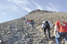 Members of the 821st Support Squadron at Thule Air Base, Greenland, hiked up the 724-foot high Thule landmark, Mount Dundas, Aug. 23 following a commander's call. The Ravens rallied at the foot of the mountain to make the climb, which took about one hour because in the final 50-feet of the climb Airmen had to use a fixed rope and go up single file, one at a time. The climb was the first of many planned team-building events for the squadron. (U.S. Air Force photo/Master Sgt. Petra Wright)