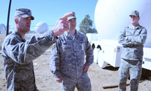 """2nd Lt. Mayo Coiner, 4th Space Operations Squadron mobile operations unit, explains to 2nd Lt. Chase Bowen, 54th Combat Communications Squadron officer in-charge of cyber operations, Robbins Air Force Base, Ga. and Staff Sgt. Ray Lena, 34th Combat Communications Squadron, Tinker Air Force Base, Okla., about Schriever's """"golf balls"""" here Feb. 11. This series of low profile antennas, more commonly called """"golf balls,"""" protects the antenna and are spherical to be able to rotate a full 359 degrees in order for 4 SOPS to be able to communicate with the MILSTAR satellite constellation anywhere in its orbit. (U.S. Air Force photo by Staff Sgt. Erica Picariello)"""