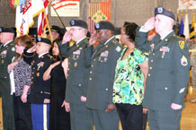 Photos by Spc. Samantha B. Koss.  Retiring Soldiers and their spouses pay respect during the national anthem at the Mountain Post Retirement Ceremony Feb. 23 at the Special Events Center.