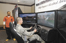 Airman 1st Class Robert Victor Smith, 721st Security Force Squadron (front), takes a spin behind the wheel of a drunken driving simulator May 13, 2011 in the Peterson Air Force Base Club while Jeremiah Newson, a Save a Life Tour manager (rear) tries to distract him. The simulator is programmed to respond as if a drunken driver was in control. The tour, which was brought to Peterson AFB in conjunction with the 21st Space Wing's 101 Critical Days of Summer safety campaign, also included a video and a Save a Life Tour alcohol survey. In the summer months, between Memorial Day weekend and Labor Day weekend, safety mishaps tend to be high. The 21st SW's campaign aims to draw special attention to safety with events and safety days throughout the summer. (U.S. Air Force/photo by Craig Denton)