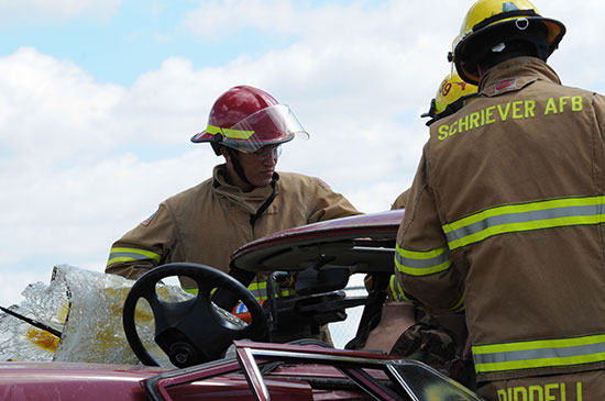 Photo by Samantha Million, Ellicott High School Student Joseph Allen, Ellicott High School student (red hat), participates in an auto extraction exercise, while members of the Schriever Fire Department supervise Friday. Allen and six other Ellicott High School students shadowed different members of the 50th Mission Support Group and public affairs during a job shadow program here.