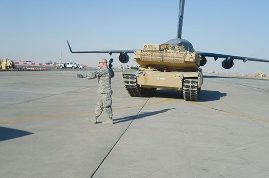 (U.S. Air Force photo by Master Sgt. Chris Campbell) Southwest Asia — Master Sgt. Bradley Hayes, 386th Expeditionary Logistics Readiness Squadron ramp operations noncommissioned officer in charge, deployed from Peterson Air Force Base, Colo., directs an M-1 tank following its offload at an undisclosed location in Southwest Asia, Sept. 26, 2013. Ramp personnel at the 386th Air Expeditionary Wing on average handle more than 3,000 tons of cargo each month.