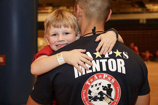 (Courtesy Photo)  A child gives his mentor a hug during a Tragedy Assistance Program for Survivors event. The mission of the program is to provide ongoing peer-based emotional support to anyone who is grieving the death of someone who died while serving in the Armed Forces.