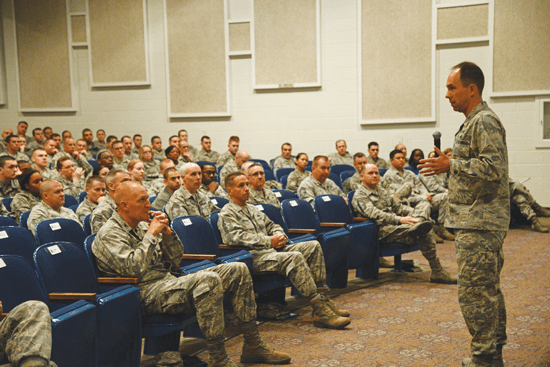 (U.S. Air Force photo/Tech. Sgt. Jared Marquis) PETERSON AIR FORCE BASE, Colo. – Col. John Shaw, 21st Space Wing commander, explains the need for various force management programs during an enlisted call Dec. 17 at the auditorium. Shaw stressed the need for transparency from Air Force leadership at all levels as the force prepares to get smaller by January 2015. In addition to the enlisted call, Shaw and personnel experts hosted an officer call on Dec. 17, and a civilian call Dec. 18 to explain officer and civilian force management programs.