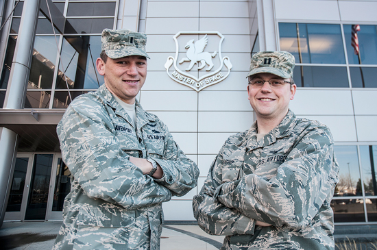 U.S. Air Force photo/Staff Sgt. Julius Delos Reyes First Lt. Gary Davenport, chief of the 50th Space Wing Commander's Action Group, and Capt. Matthew Manship, 22nd Space Operations Squadron network crew commander, pose for a photo Tuesday, in front of the 50 SW DeKok headquarters building here at Schriever Air Force Base. The officers were selected for the Lieutenant General Forrest S. McCartney Spacelift Education & Crossover Program, or SLEC-P. They will be assigned to a leading commercial space launch company for one year and then return to the Air Force, bringing their unique experiences into their follow on assignments at the Space and Missile Systems Center, Los Angeles Air Force Base, Calif.