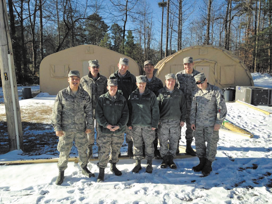 (U.S. Air Force photo) DOBBINS AIR RESERVE BASE, Ga. — Six Airmen from Peterson AFB, along with their fellow trainees, stand in front of the tents where they slept and prepared more than 800 hot meals to personnel and emergency responders stranded on base during a rare snowstorm that crippled the Atlanta region. The uncommon snowfall in the region forced Dobbins ARB to shut down for two days, leaving many without vital services.