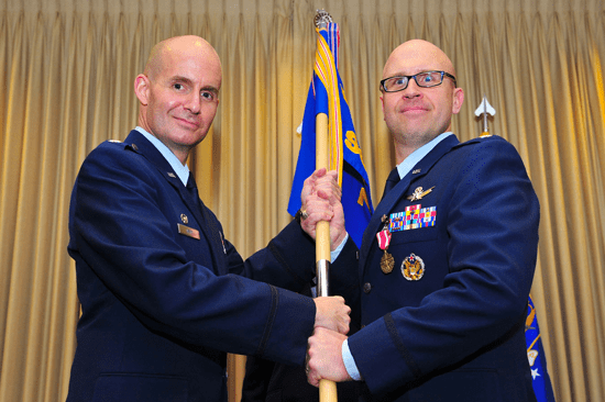 Air Force Reserve Lt. Col. Michael A. Assid, acting 310th Operations Group commander (left), presents the 7th Space Operations Squadron guidon to AF Reserve Lt. Col. Kent Leonard Saturday, on Schriever Air Force Base, Colo. Leonard assumed command of the squadron during the ceremony.