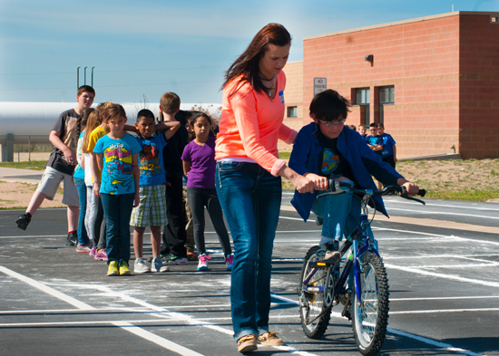 U.S. Air Force photo/Senior Airman Naomi Griego Airman 1st Class Kayla Elliott, 50th Security Forces Squadron, helps an Ellicott Elementary School student ride a bike during the school's bike rodeo May 19, 2014, in Ellicott, Colo. Elliott and other Airmen from Schriever Air Force Base volunteered to spend the teach fourth-graders how to ride a bike.