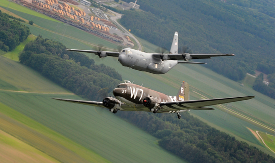 (U.S. Air Force photo/Staff Sgt. Sara Keller)  A Douglas C-47 Skytrain, known as Whiskey 7, flies alongside a C-130J Super Hercules from the 37th Airlift Squadron May 30, 2014, over Germany. The C-47 came to Ramstein Air Base, Germany, for a week to participate in base activities with its legacy unit, the 37th Airlift Squadron, before returning to Normandy to recreate its role and drop paratroopers over the original drop zone in Sainte-Mere Eglise, France.