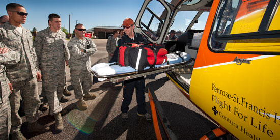(U.S. Air Force photo/Craig Denton)  PETERSON AIR FORCE BASE, Colo. -- Rod Gano, Flight for Life Colorado paramedic, shows fire prevention technicians from the 21st Civil Engineer Squadron how to slide out a stretcher from the Flight for Life helicopter here June 13. Flight for Life Colorado held a training session with the local fire prevention team to gain familiarization with their operations in the event a patient needs rapid transport.