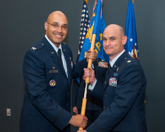 (U.S. Air Force photo/Craig Denton)  PETERSON AIR FORCE BASE, Colorado – Col. David Miller Jr. (left), 21st Operations Group commander, passes the 4th Space Control Squadron guidon to Lt. Col. Eric Lingle, 4th SPCS commander, during the squadron's change of command ceremony here July 11. Lingle assumed command of the 4th SPCS, which provides combat space superiority effects to the commander, Joint Functional Component Command – Space and theater combatant commanders.