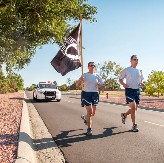(U.S. Air Force photo/Craig Denton) PETERSON AIR FORCE BASE, Colo. - Col. John Shaw, 21st Space Wing commander, and Chief Master Sgt. Idalia Peele, 21st SW command chief run with the POW flag following the POW/MIA recognition retreat ceremony Sept. 18. Members of the 21st SW held a reveille and retreat ceremony recognizing the sacrifices of POWs and MIAs.