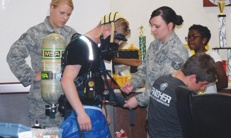 (U.S. Air Force photo by Dave Smith) PETERSON AIR FORCE BASE, Colo. – Staff Sgts. Katherine Streepy (left), and Staci Eckert, 21st Medical Group Bioenvironmental Engineering Flight technicians, help Ryan Weatherbee suit up in a protective suit used in their line of work. The 21st MDG marked Bring Your Child to Work Day April 23 to showcase its mission capabilities.