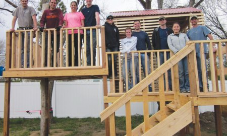 (Courtesy photo by Pati Nuce) PETERSON AIR FORCE BASE, Colo. – Members of the Company Grade Officer's Council pose for a photograph after completing a playground for Sarah's Home, April 25, 2015. The volunteers designed and built an elevated club house, zip line, high bars, dual swings and a tight rope for the home that fosters underage female sex trafficking victims.