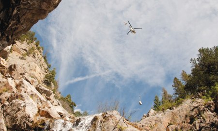 """(U.S. Air Force photo by Senior Airman Tiffany DeNault) CHEYENNE MOUNTAIN AIR FORCE STATION, Colorado – A """"Lama"""" helicopter designed for high elevation, lifts equipment in and out of the canyons where ring nets are to be installed, May, 28, 2015. The five ring nets are one of four steps in the mitigation process to reduce the damage of future landslides. The ring nets, 15-foot deep main catchment basin, a culvert down the mountain into the storm water system and infrastructure protection are being built as a result of landslides that struck the mountain Sept. 12, 2013, following torrential rain."""
