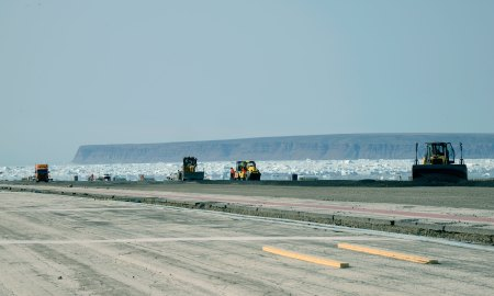 (U.S. Air Force photo by Tech. Sgt. Jared Marquis) THULE AIR BASE, Greenland – Contractors work to upgrade the Thule Air Base runway July 11, 2015. The first half of the project – the first 5,000 feet of the 10,000 foot runway – began in early June and is scheduled to be completed by Sept. 15. The second half of the upgrade will begin next year.
