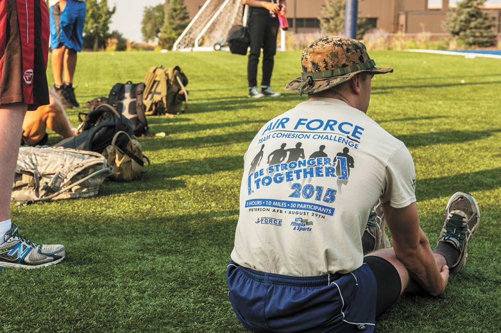 PETERSON AIR FORCE BASE, Colo. — Participants in the Air Force Team Cohesion Challenge stretch and prepare for intense mental and physical tasks behind the base Fitness Center, Aug. 29, 2015. The challenge required participants to load a rucksack with weight and compete in roughly five hours of team building events that covered a distance of seven to ten miles. Each task given wasn't something that could be completed on their own, so participants had to become a solid team and work together. (U.S. Air Force photo by Airman 1st Class Rose Gudex)