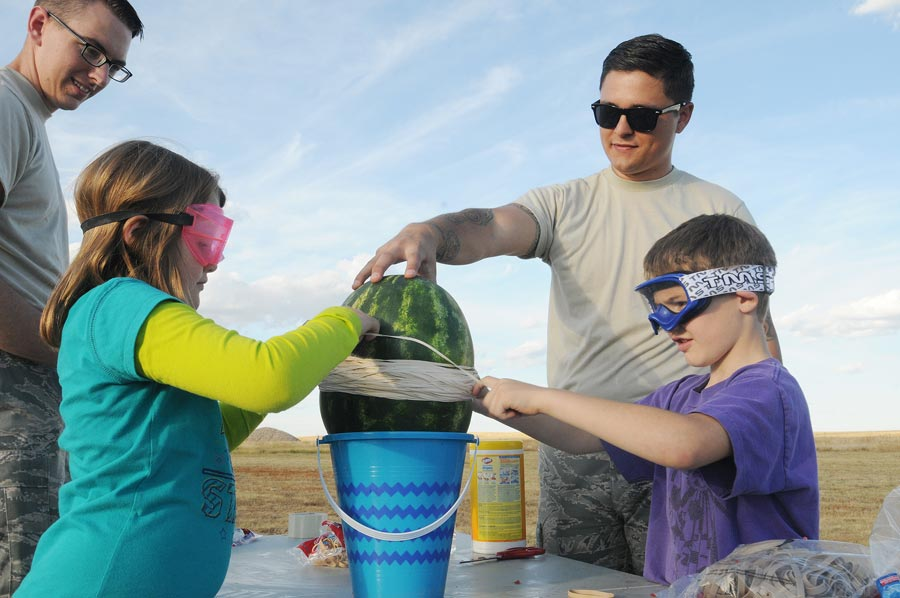 U.S. Air Force photo/2nd Lt. Darren Domingo Schriever Airmen assist Kayden Rice (second from left) and Brodie Rice (right) place hundreds of rubber bands around a watermelon to create a pressure explosion during science, technology, engineering and mathematics night Thursday, Oct. 8, 2015, outside the Schriever Child Development Center. The STEM night was hosted by organizations from AmeriCorps and the Colorado chapter of 4-H to introduce kids to STEM career fields.