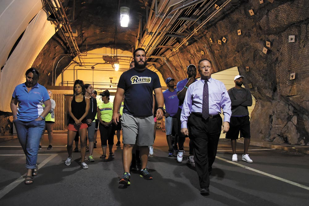(U.S. Air Force photo by Airman 1st Class Dennis Hoffman) CHEYENNE MOUNTAIN AIR FORCE STATION, Colo. — Steven Rose, 721st Mission Support Group deputy commander, guides NFL players on a tour of Cheyenne Mountain Air Force Station, Colo., July 13, 2016. The players toured the facilities as a part of the CMAFS 50th year celebration.