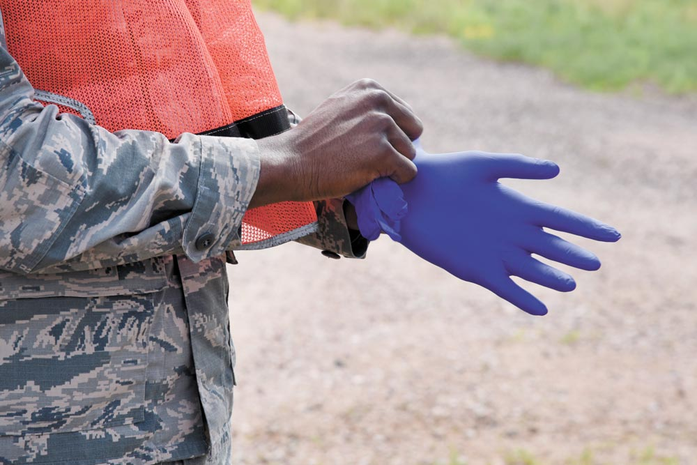 PETERSON AIR FORCE BASE, Colo.  —  A 21st Force Support Squadron Airman puts on gloves for a search and recovery exercise at Peterson Air Force Base, Colo., July 14, 2016. The training exercise consisted of FSS Airmen and officers from Peterson AFB, Schriever AFB and representatives from the El Paso County Coroner's Office.
