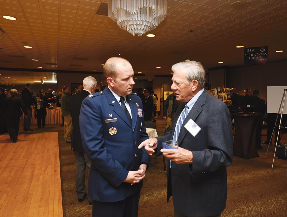 (U.S. Air Force Photo by Philip Carter) PETERSON AIR FORCE BASE, Colo. — 21st Space Wing Commander Col. Doug Schiess discusses a point from his State of the Wing address with retired Maj. Gen. Wes Clark, former vice commander of Air Force Space Command. Schiess presented the address to community leaders Thursday, Oct. 6 as a review of his first fiscal year in command, as well as a glimpse into the upcoming year.