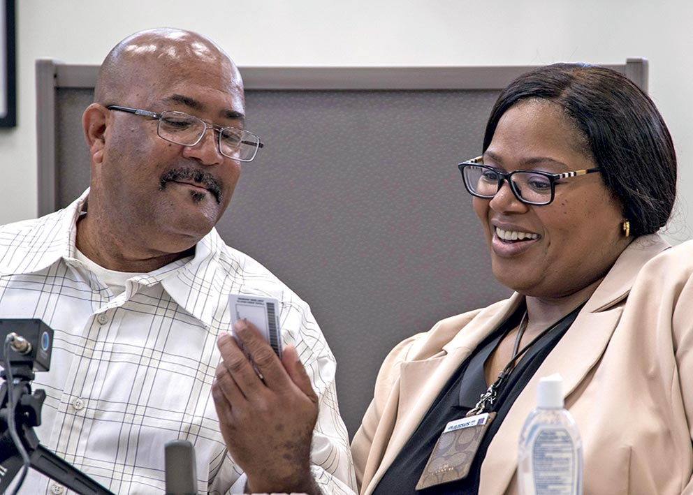 (U.S. Air Force photo/Senior Airman Jordyn Fetter) Joint Base Andrews, Md.  — Michael L. Chavis, a Gold Star parent, shows his new Gold Star Base Access ID card to Carla Diamond, a U.S. Air Force Headquarters community readiness consultant, at Joint Base Andrews, Md., May 1, 2017. These cards are part of an Air Force initiative allowing Gold Star family members, immediate relatives of deceased Airmen, unescorted access to Air Force installations to visit buried loved ones, attend base events, and stop by Airmen and Family Readiness Centers for support.
