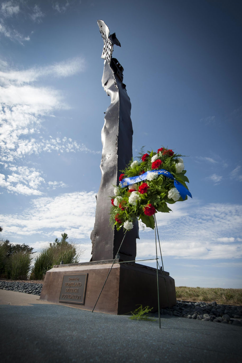 U.S. Air Force photo/Dennis Rogers A wreath sits on display in front of a monument, crafted from a steel beam salvaged from the World Trade Center attacks, during the Pikes Peak Area 9/11 commemoration ceremony 'A Community Remembers' at Schriever Air Force Base, Colorado, Monday, Sept. 11, 2017. The wreath laying focused on the somber memories of that day, never to be forgotten. Don Addy, chairman of the Colorado Thirty Group, secured the steel beam for the monument during his tenure as the National Homeland Defense Foundation president.