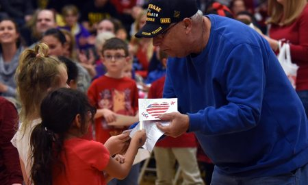 U.S. Air Force photo by Airman 1st Class William Tracy Ellicott students give thank you letters and hand-made flags to a Vietnam veteran during the Ellicott School District Veteran's Day ceremony at Ellicott, Colorado, Nov. 9, 2017. The Ellicott community event honored veterans, both past and present.