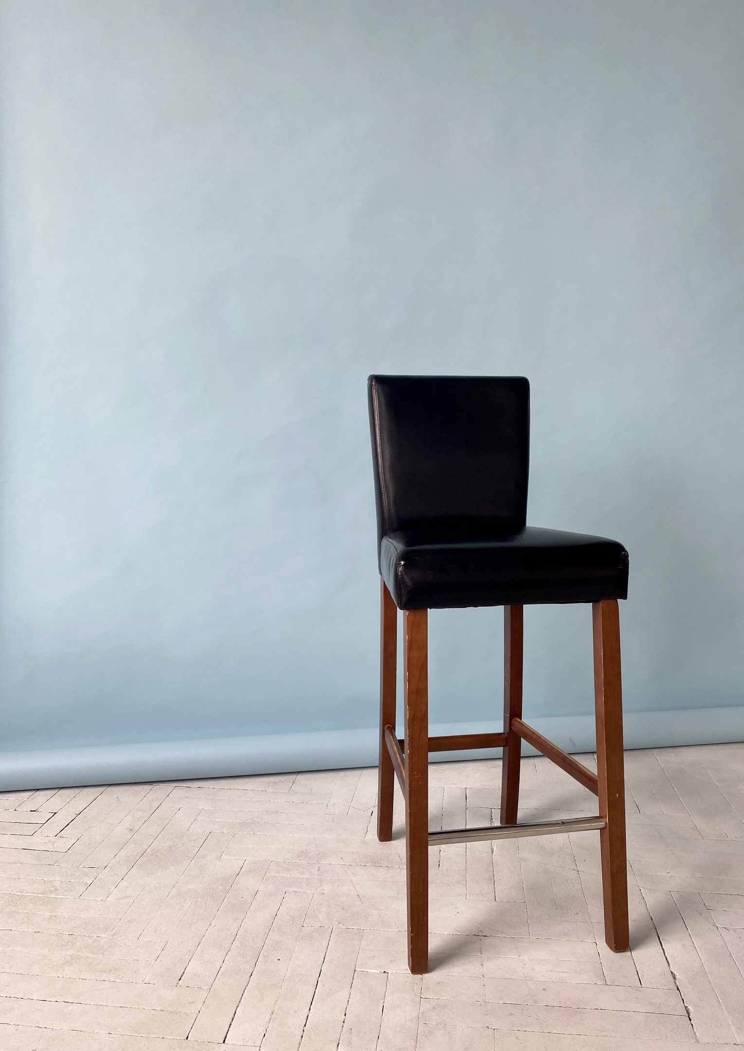 A tall black leather chair with a back and four brown legs against a light blue background.